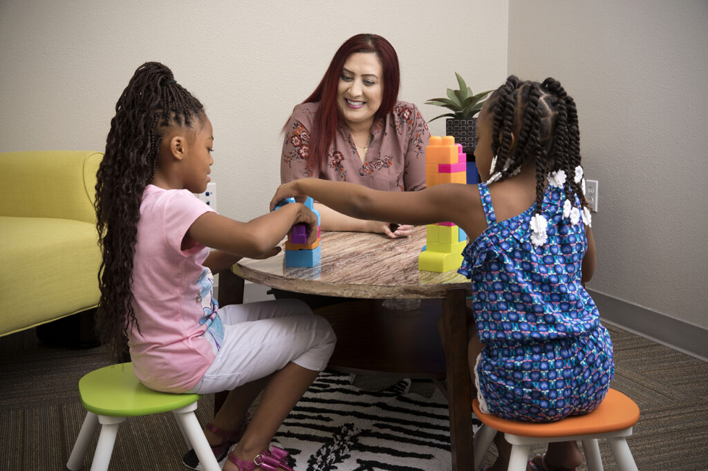 A staff member sits with two young girls.