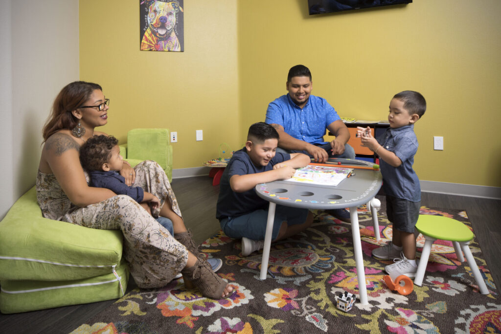 Mother and father watch their children play inside a brightly colored room